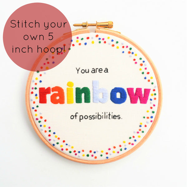 A wooden embroidery hoop with the quote You are a rainbow of possibilities  with the word rainbow in bold rainbow coloured letters with a coordinating french knot border.