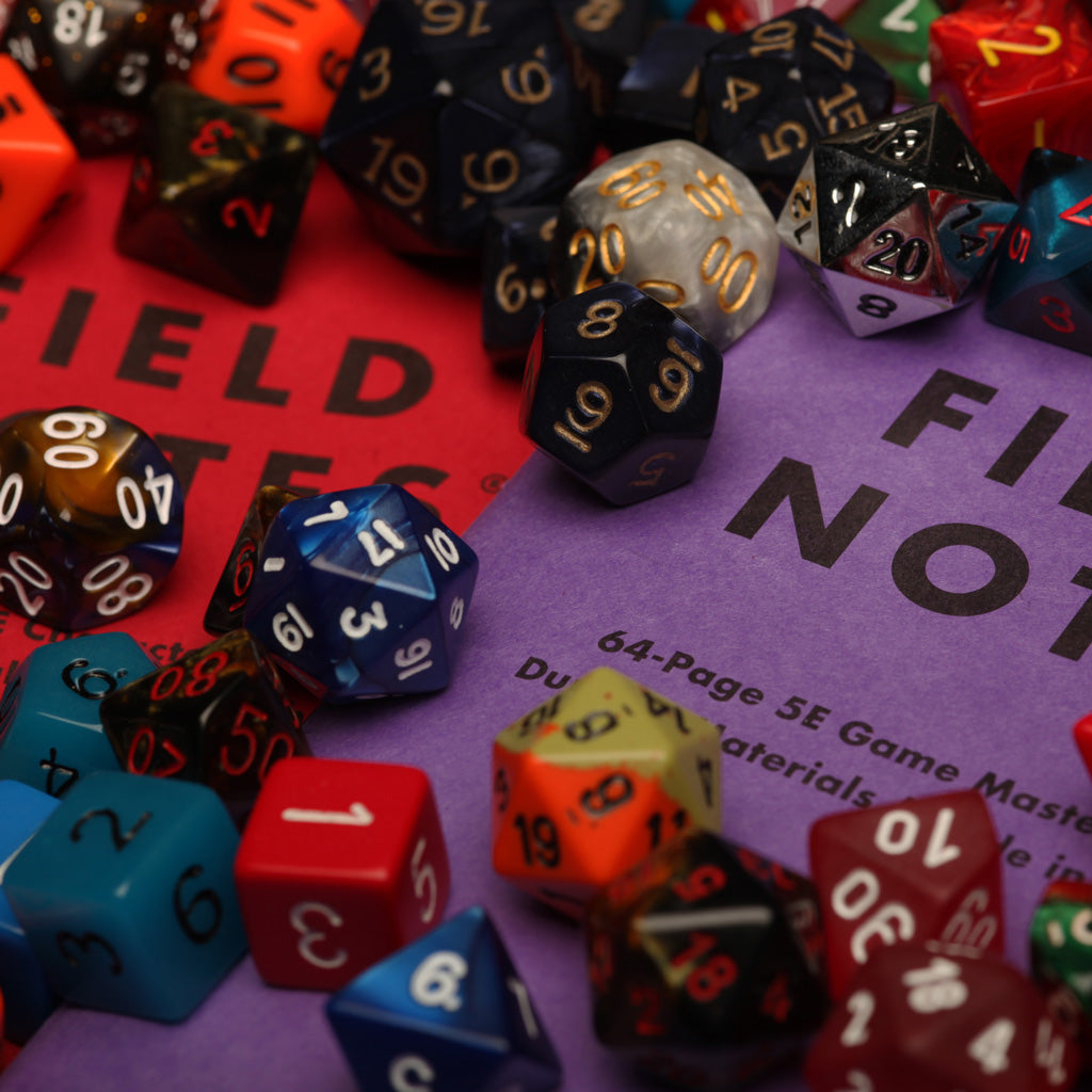 Field Notes 5E Gaming Journals covered in dice