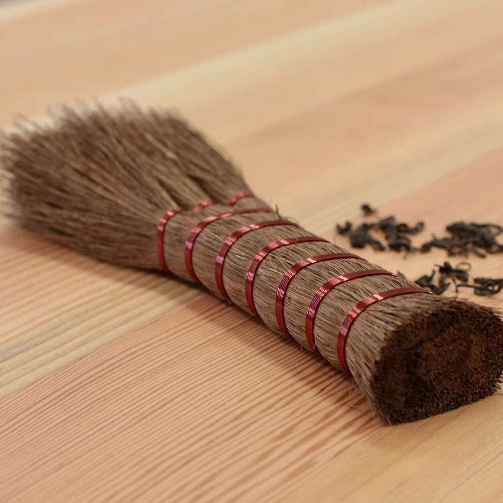 Shuro Hand Broom made from palm fibres on table