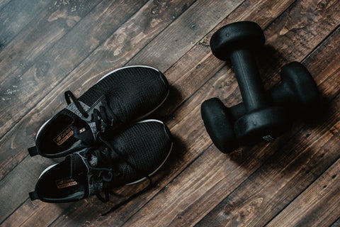 A photo of black sneakers and two black 5-pound weights