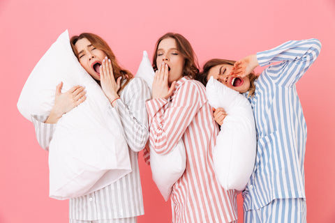 Picture of three women in pajamas yawning and holding pillows