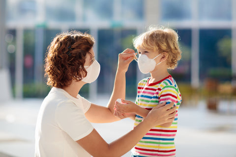 A mother with a face mask on putting a face mask on her child