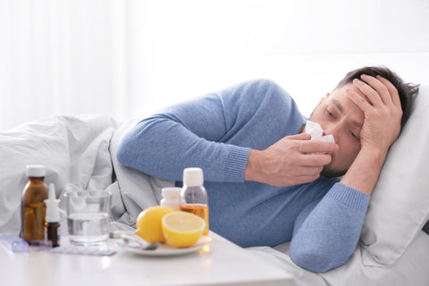Man sick in bed with medicine next to him