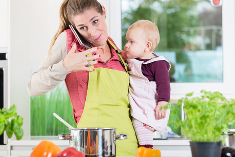A stressed out mom in the kitchen holding a baby and trying to talk on the phone
