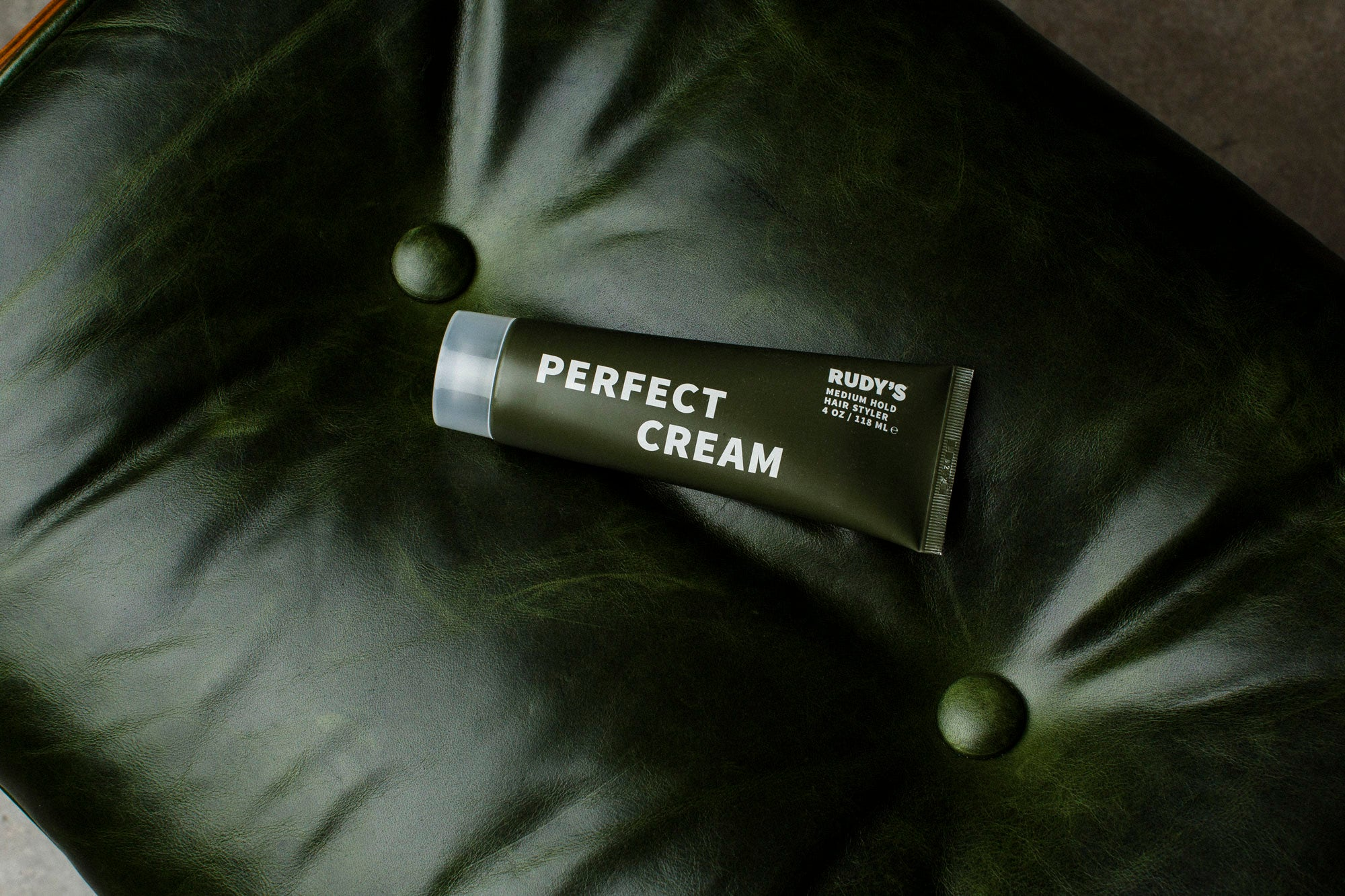 Image of Perfect Cream tube lying on green leather chair