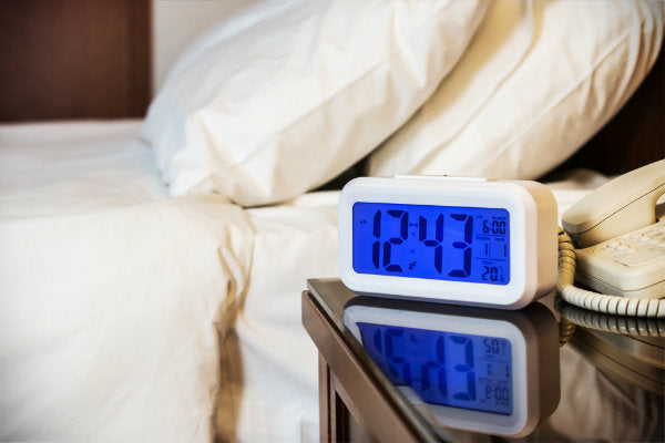 Alarm clock and bed to illustrate CBD for sleep