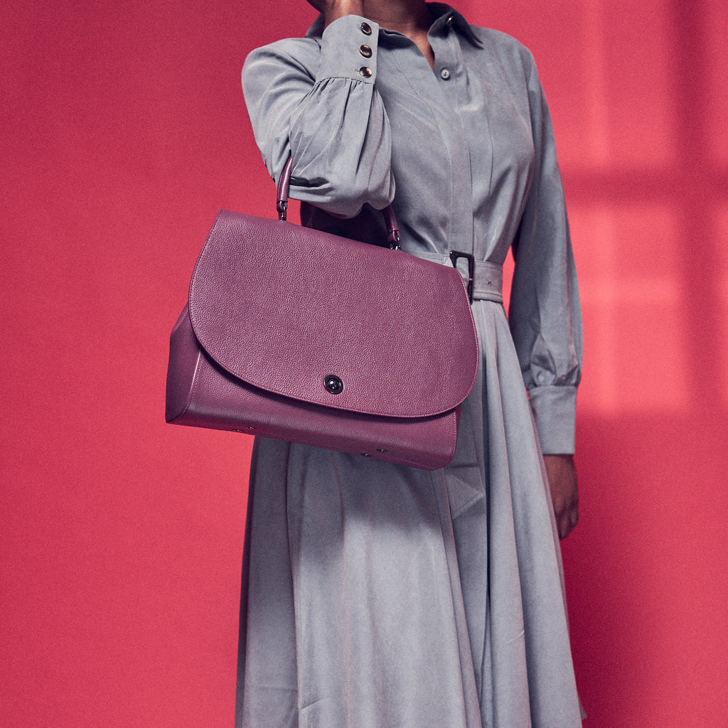 A fashion and style editorial photo showing a woman model holding a burgundy red leather handbag. The bag has a minimalist design with a trapeze shape and rounded oversized flap. This is the Tomoli Briffani Jut interchangeable satchel in Sangria.