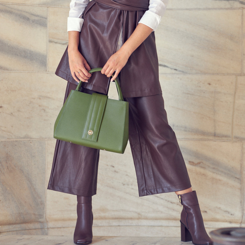 A fashion and style editorial photo showing a model wearing a brown faux leather outfit and holding an olive green handbag. The bag has a minimalist design and a skinny quilted closure down the middle. The overall look is color-blocked with brown and green. The bag is the Tomoli Briffani Lean interchangeable closure tote in Olive.