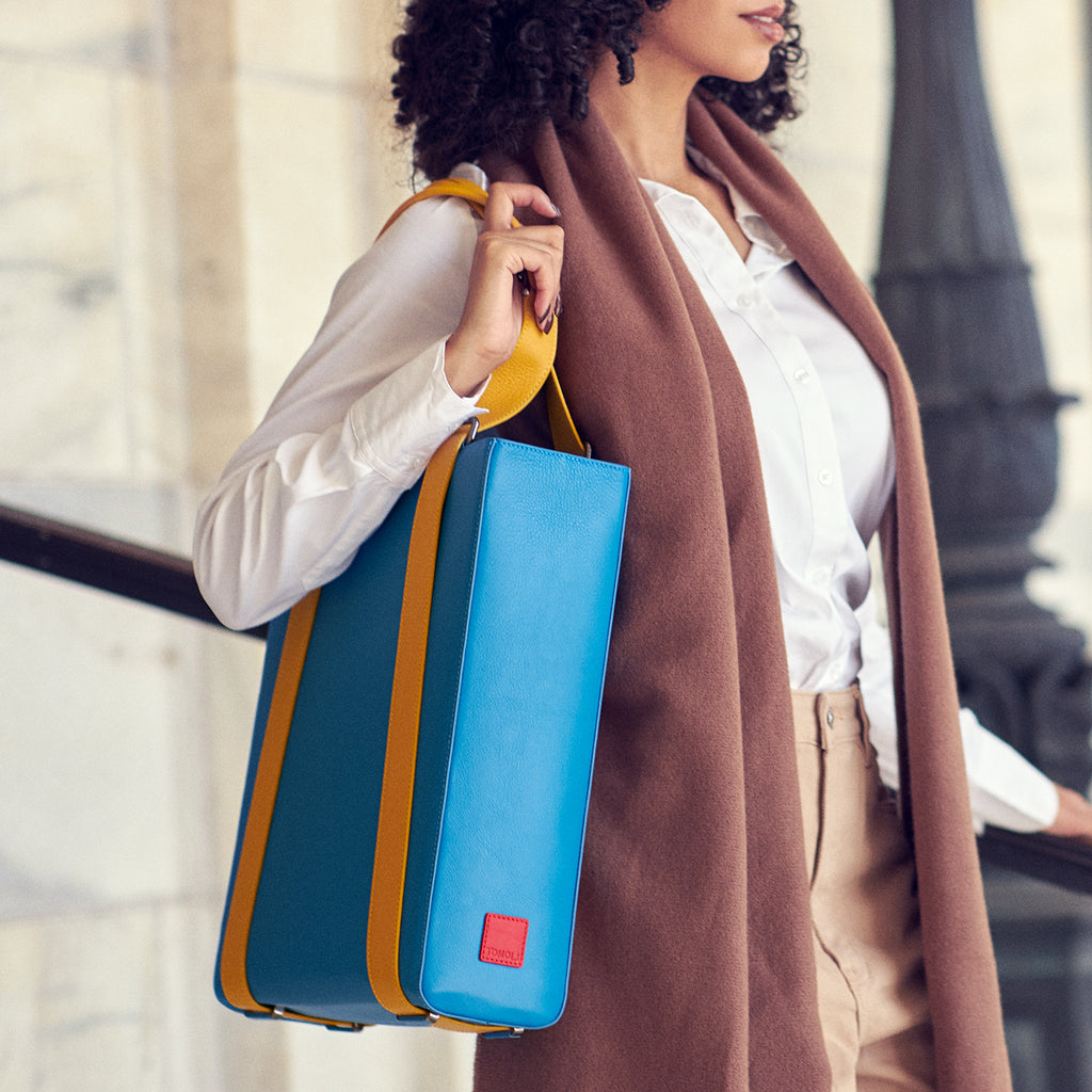A fashion and style photo showing a woman wearing a neutral Fall outfit and a colorful leather tote handbag over her shoulder. The bag is primarily blue and has a structured briefcase-case like shape that is color-blocked with yellow straps. Overall, the bag adds a pop of color to the woman's outfit. This is the Tomoli Kora convertible leather tote in Golden Sky.
