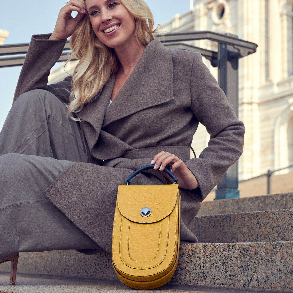 A fashion and style editorial photo showing a woman wearing a neutral Fall outfit with a yellow leather handbag. Th bag has an elongated saddle shape and is color-blocked with a blue top handle. This is the Tomoli Fitini II elongated saddle bag in Shady Maize.