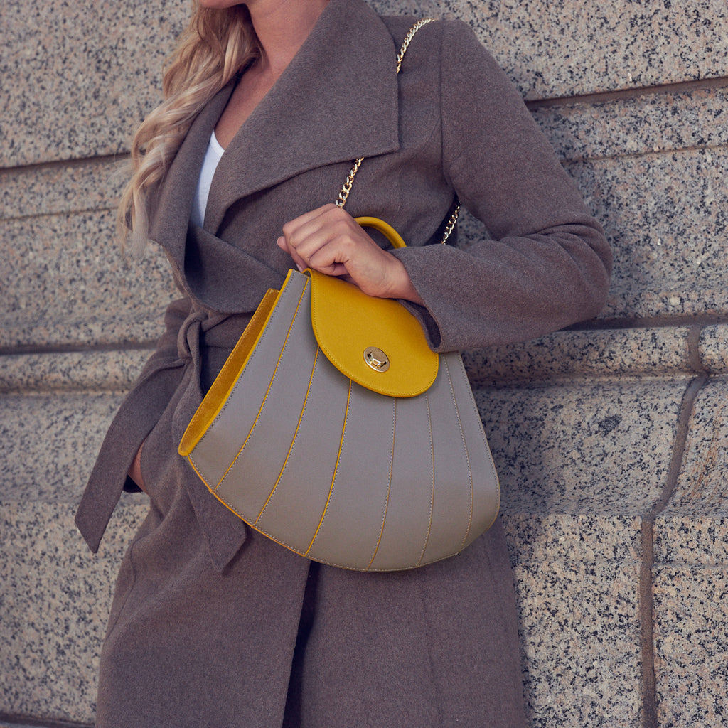 A fashion and style editorial photo showing a woman wearing a neutral Fall outfit and holding a yellow and beige leather handbag. The handbag has a rounded trapeze shape that resembles a seashell. The body is a neutral beige color with yellow radial lines, and the flap closure is yellow. The woman is wearing the bag over her shoulder with the chain strap. This is the Tomoli Gisel tapered top handle handbag in Sun Stone.