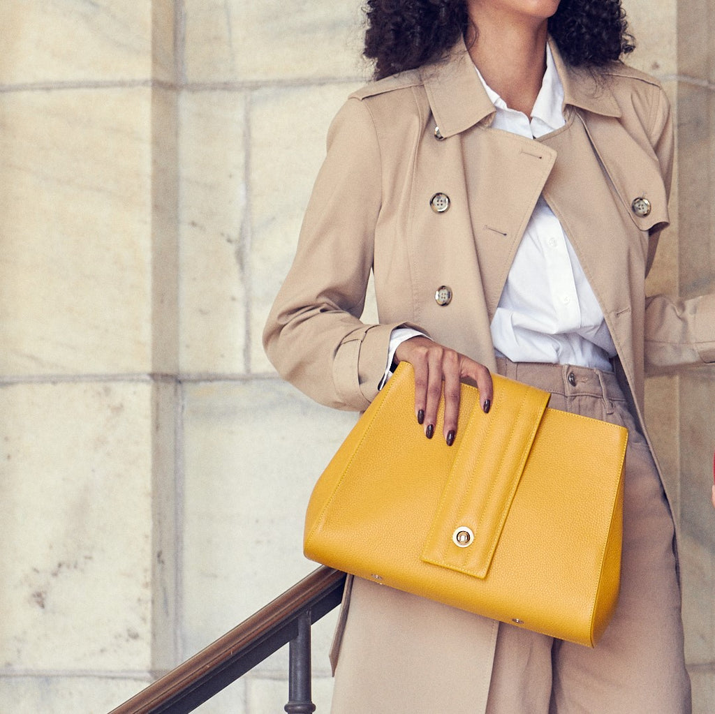 A fashion and style editorial photo showing a woman wearing a neutral outfit and holding a yellow handbag. This is the Tomoli Briffani Lean interchangeable closure tote in Maize. This bag is lightweight, fits a laptop, and makes the perfect everyday bag.