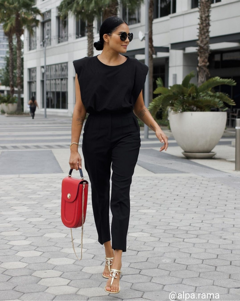 A fashion and style editorial photo showing a woman wearing a black outfit with a red leather handbag. The handbag has an elongated round silhouette and a flap closure. This is a red and black color-blocked outfit. The handbag is the Tomoli Fitini II elongated saddle bag in Shady Red. This bag has a mini shape that can be worn as an everyday bag, or a night-out bag.