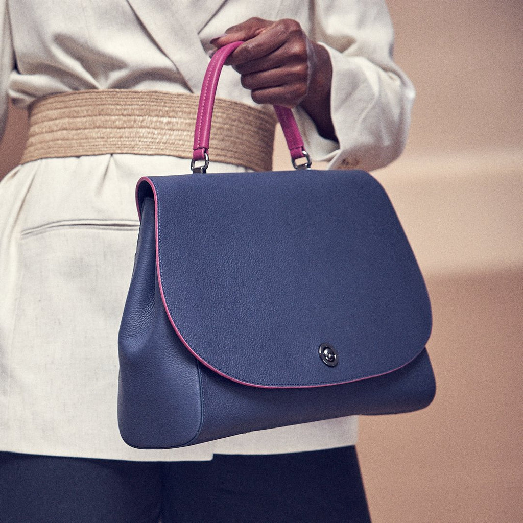 A fashion and style editorial photo showing a model holding a dark blue leather handbag. The handbag is color-blocked with a pink handle and pink edges. This leather satchel is light, fits a laptop, and makes the perfect everyday bag.