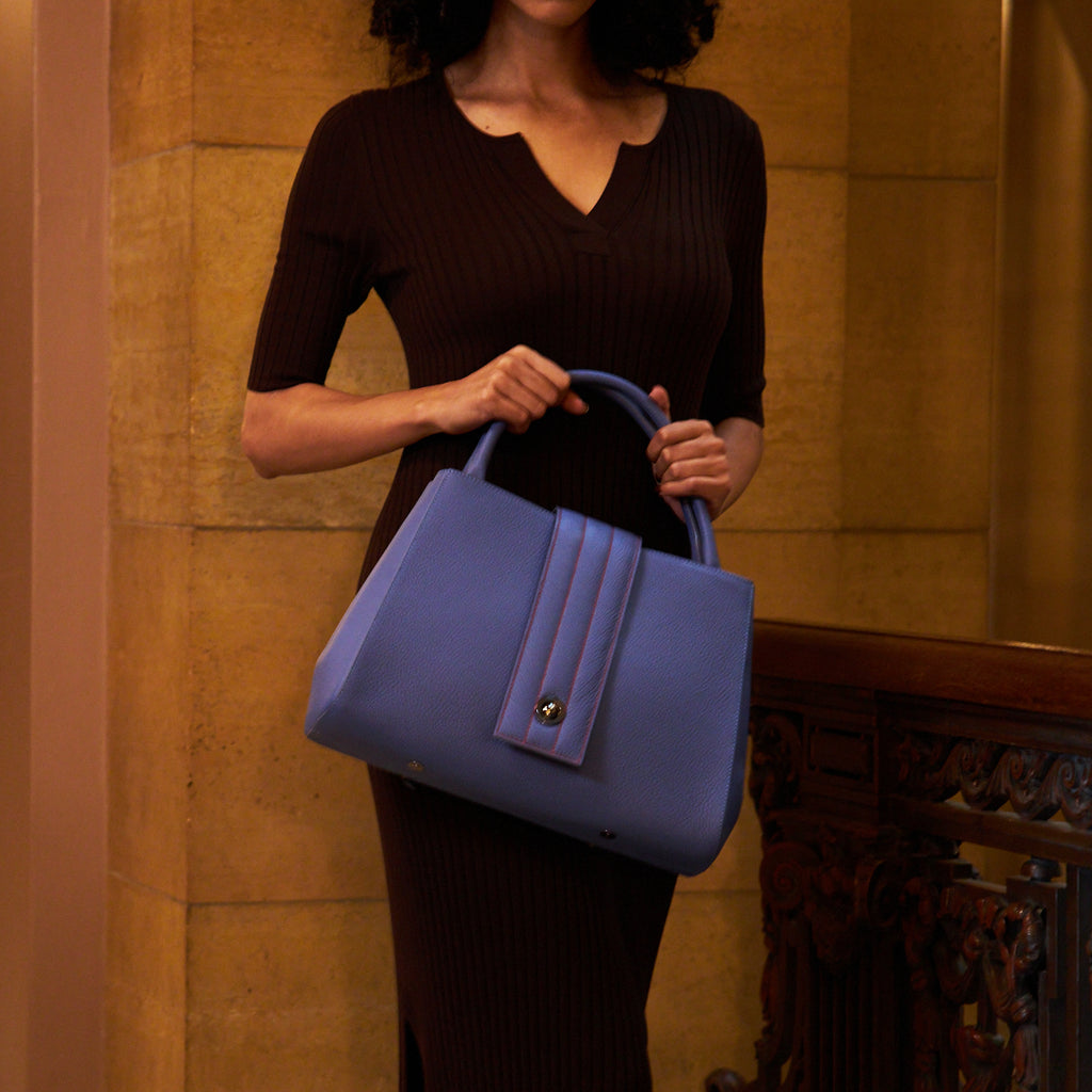 A fashion and style editorial photo showing a woman wearing a dark fitted outfit with a blue purple leather bag. The handbag is an interchangeable quilted closure tote. This is a bag ready for night out, everyday errands, or office wear. The handbag is the Tomoli Briffani Lean interchangeable quilted closure tote in Hot Iris.