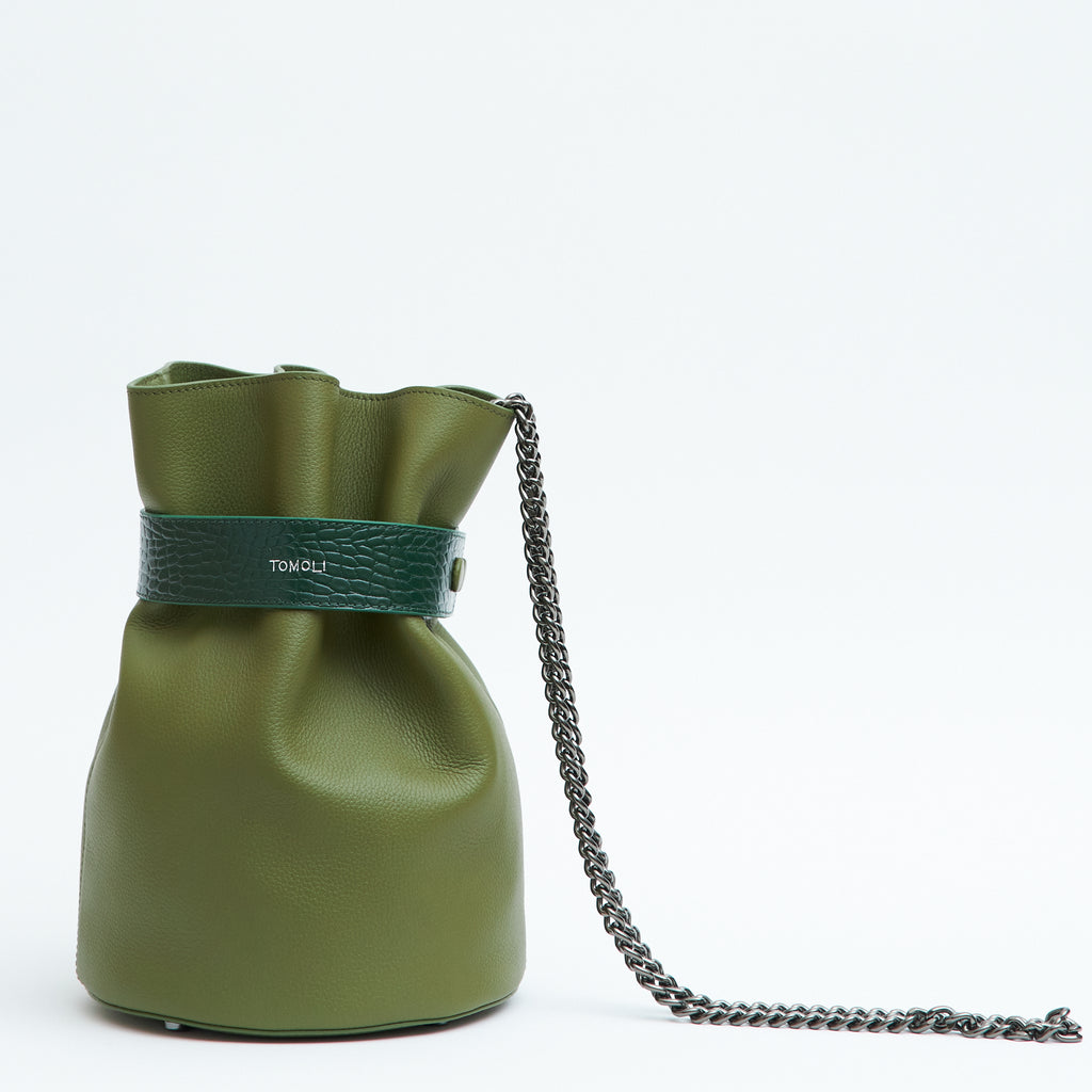 A product photo showing the front view of a leather bucket bag. The bag is olive green and has a wide belt towards the top that creates a cinched effect. The word TOMOLI is stamped in the center of the belt. There is a chain strap in gunmetal color.