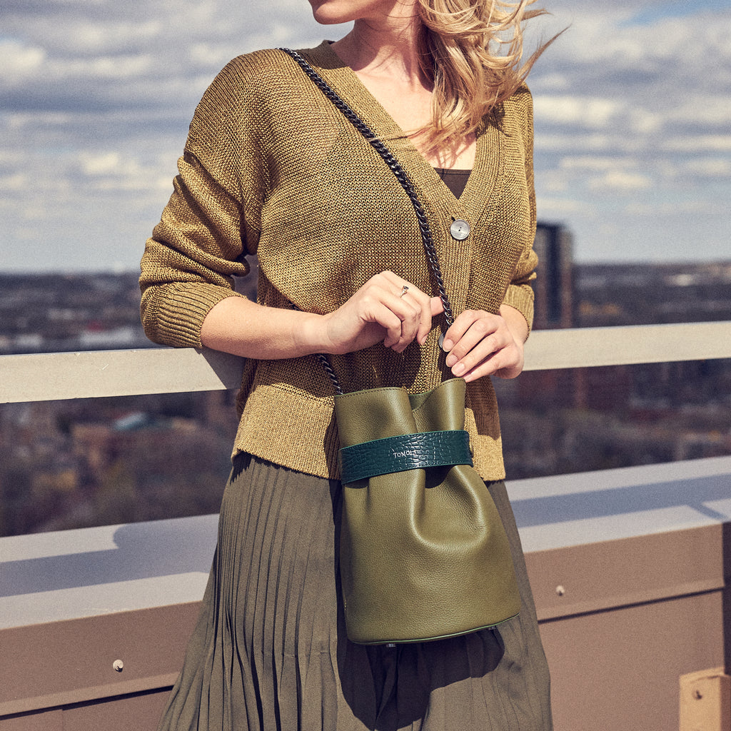 A handbag fashion editorial photo showing a model wearing a monochromatic olive green outfit with an olive green bucket bag. The bucket bag has a bold belt across the top and a chain strap.