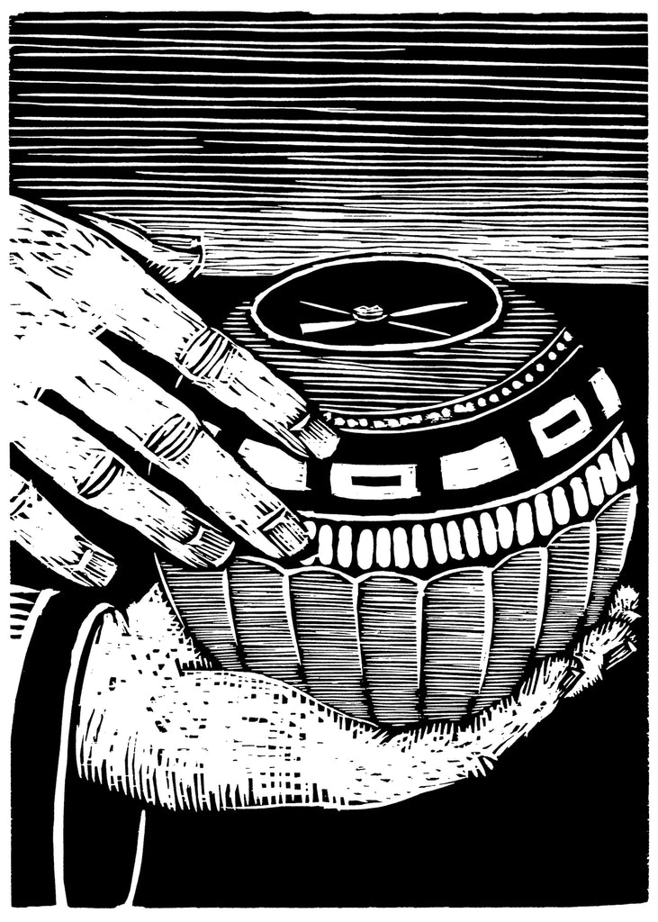 Black and white woodcut of a a carved ball with a compass being held by a hand.