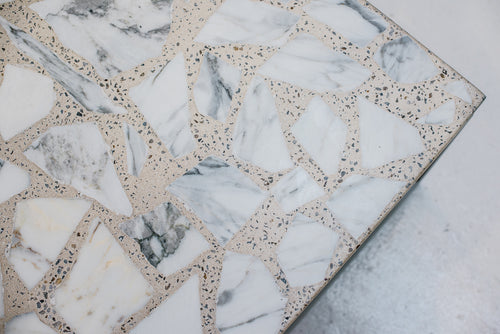Detailed image of the Alpha Terrazzo Coffee Table. The large marble aggregate is shaped and hand-set into concrete. The result is a jewel-like surface, distinctly unique with no two tables ever sharing the same variation.