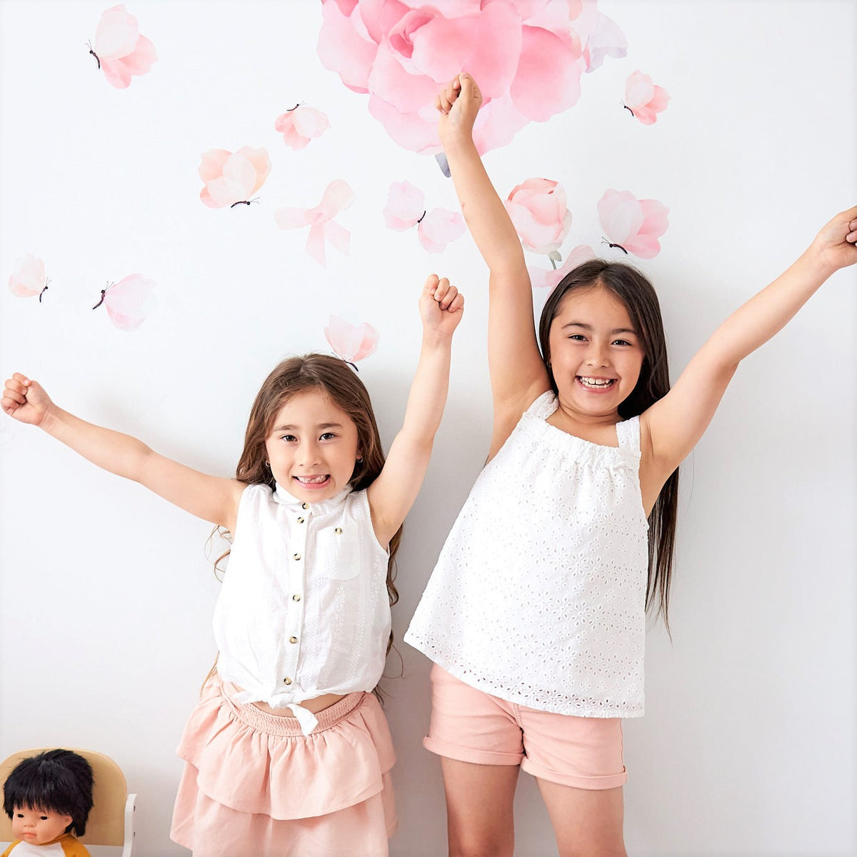 Two young girls are standing with their hands in the air with a white wall behind them. large floral pink wall decals and butterfly decals are behind them on the wall. A doll with black hair is sitting in a highchair next to the youngest girl.
