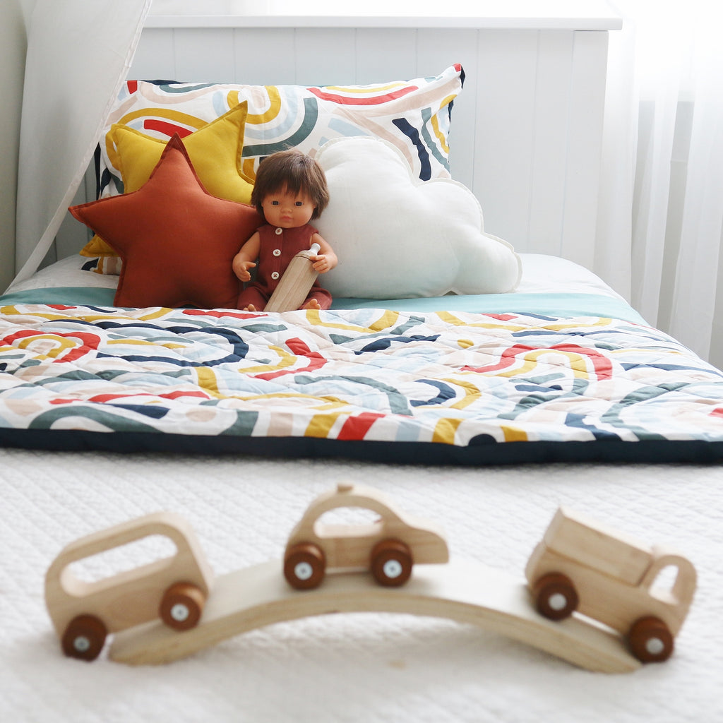 A Colourful Kids' Room with bright cushions on bed and babydoll with wooden toy bottle