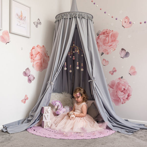 Grey canopy hanging from the ceiling in girls bedroom as reading nook with young girls sitting under canopy