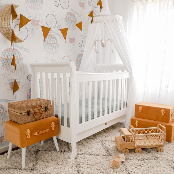 white round canopy draped over white cot in gender neutral baby nursery