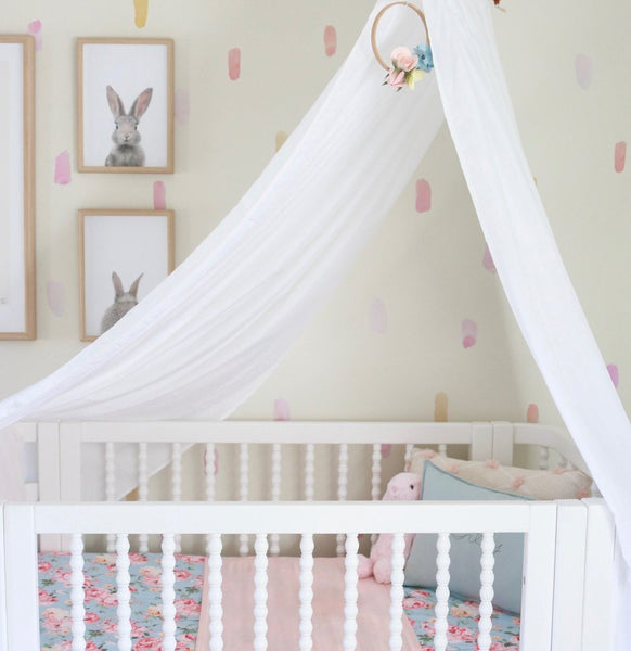 white drape canopy hanging over white cot in baby girls nursery with three picture frames on the wall above cot