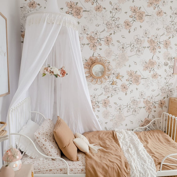 White canopy draped over white metal bed in girls bedroom
