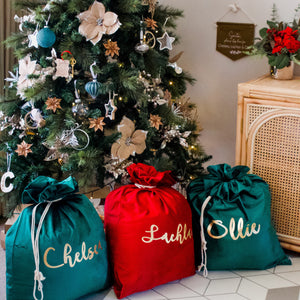 Three christmas santa sacks under a christmas tree