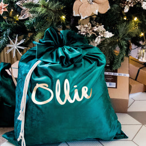 green santa sack personalised with the name ollie in gold font sitting under a christmas tree