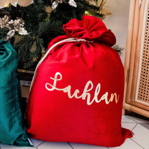 red santa sack personalised with the name lachlan sitting next to a green sack under a christmas tree