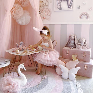 little girls playing in her bedroom with pink canopy and pink storage cases