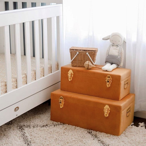 two terracotta coloured storage cases with gold clasps sitting on floor of babies nursery