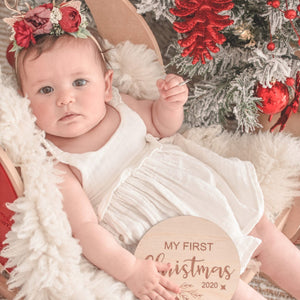 baby girl holding a mdf round disc engraved with the words my first christmas