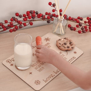 childs hand placing orange carrot onto wooden santa tray with half glass of milk and choc chip cookie
