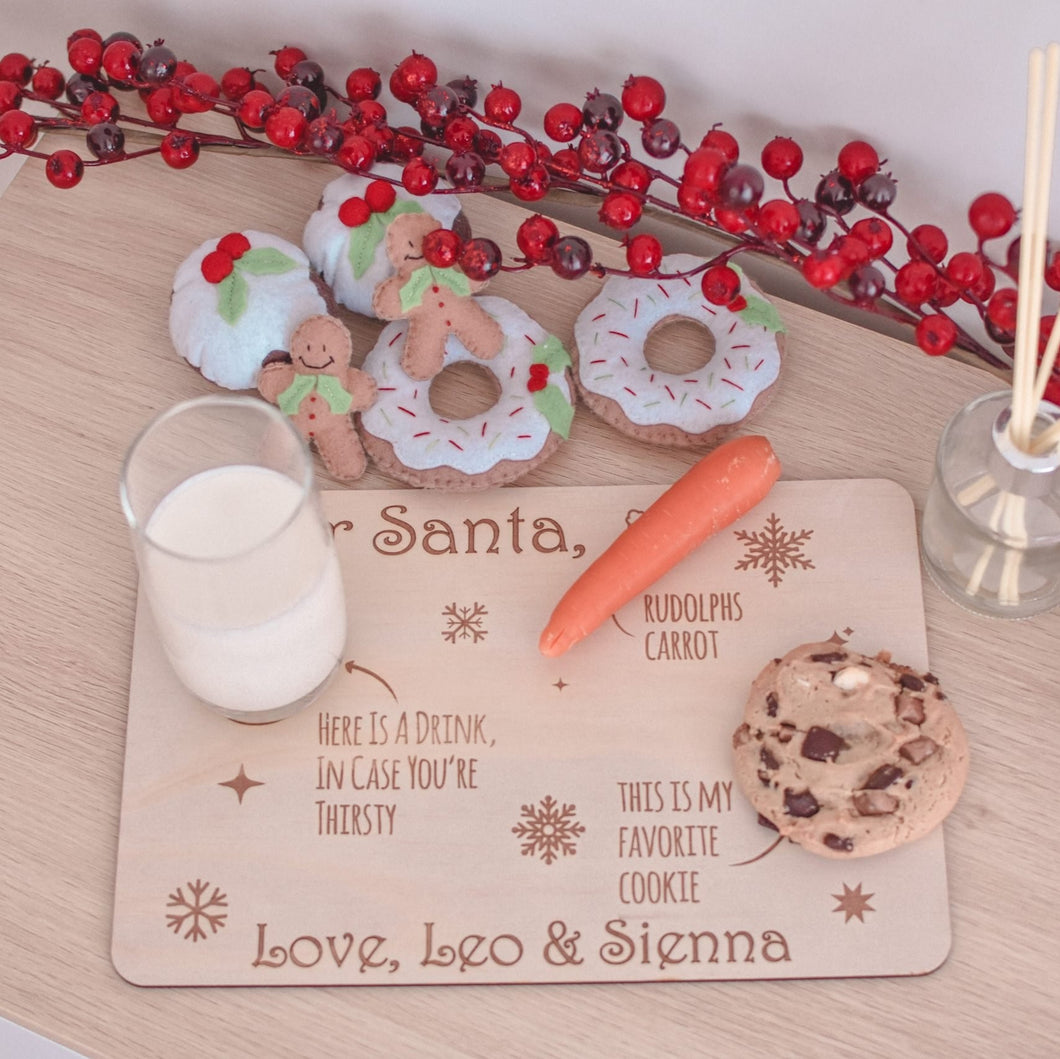 Wooden santa tray sitting on table with half glass of milk, one orange carrot and a choc chip cookie sitting on top