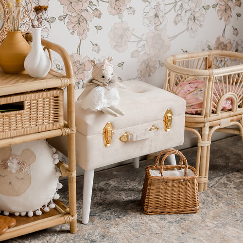 girls bedroom with bone storage stool sitting between dolls bed and wicker shelf