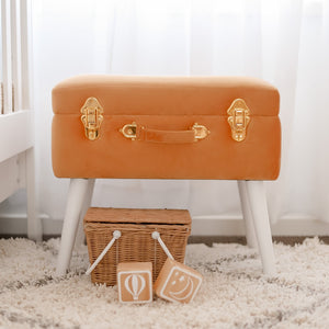 terracotta storage stool in nursery with wicker basket and wooden blocks in front on the floor
