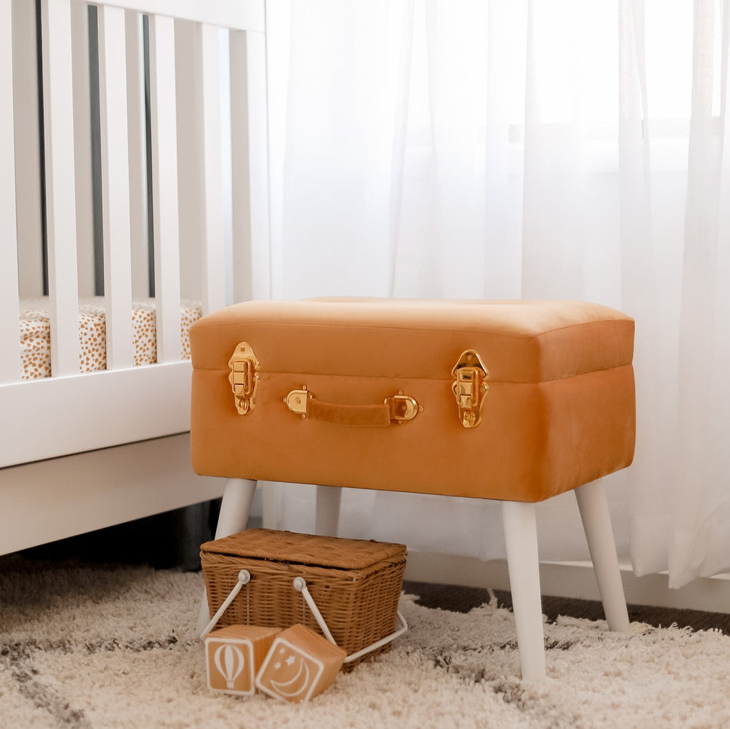 terracotta coloured stool in neutral nursery with basket and blocks
