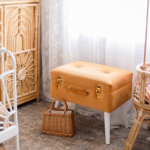 terracotta storage stool with gold clasp in girls bedroom with small handbag on ground