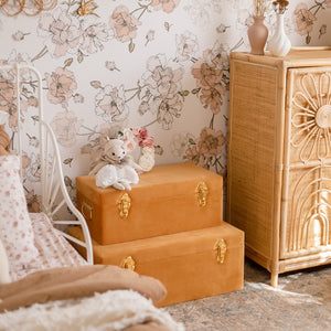 two terracotta storage boxes sitting on the floor of girls bedroom with toy sitting on top
