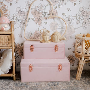two dusty pink storage cases with rose gold handles sitting on the floor of a girls bedroom with a rattan tea set on top