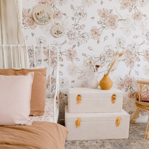 girls bedroom with set of two bone storage cases sitting on floor next to bed and vase of flowers ontop
