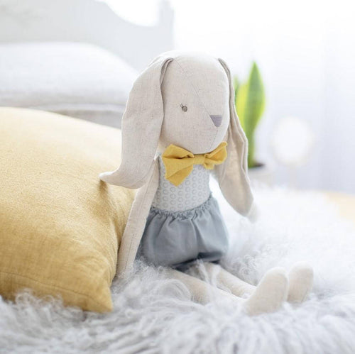 linen soft toy rabbit sitting on bed with mustard bow and grey linen shorts