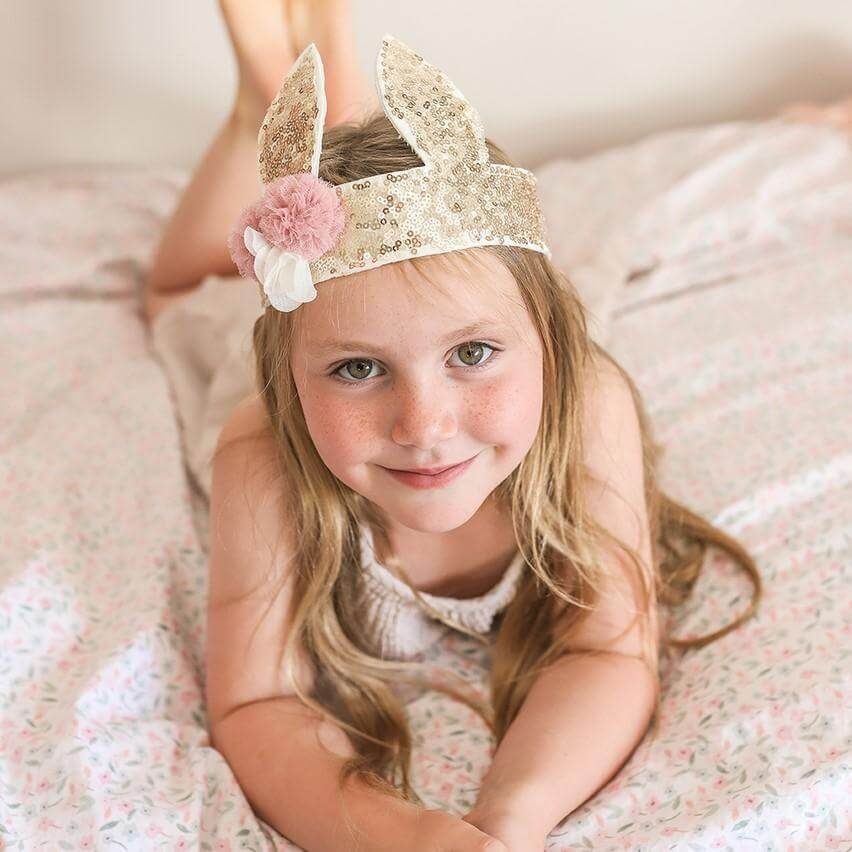 girl laying on bed wearing gold sequin bunny crown