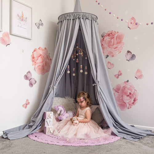Grey Round Canopy over reading nook with large rose decals on wall and girl in tulle dress sitting on cushions underneath with a purple crochet rug on floor.