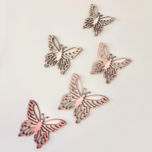 Five pink timber butterflies in various sizes attached to wall.