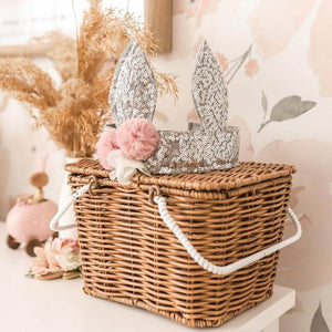 silver sequin bunny crown sitting on top of brown cane basket in child's bedroom