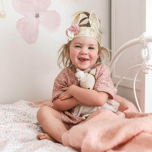 toddler on bed with gold sequin cunny crown on head and holding soft toy